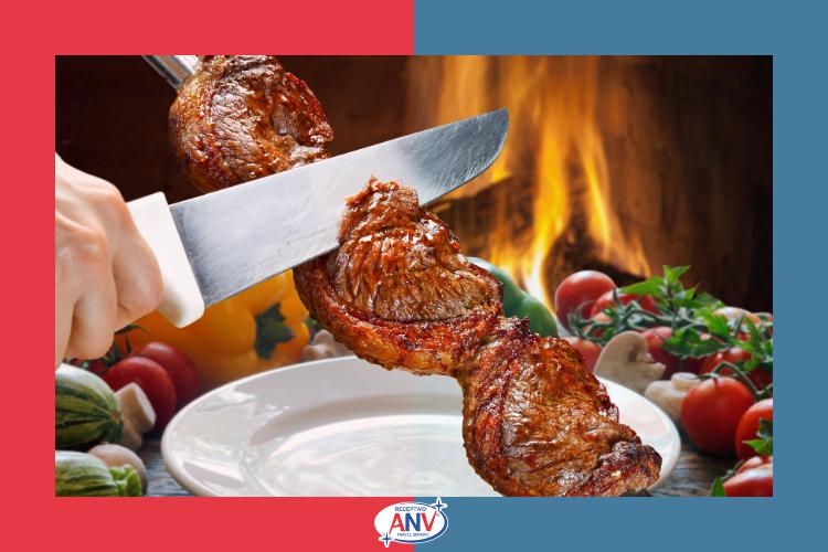 Carne no espero com legumes ao lado e ao fundo, o fogo   Restaurantes em Foz do Iguaçu